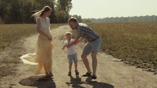 Loving family walking on countryside road. Father rotates his little son in his arms, then throws him up and catches him