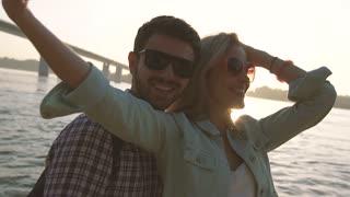 Loving traveling couple taking selfie against river and bridge