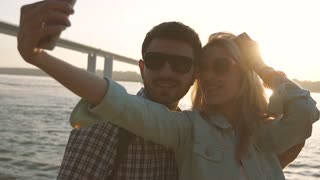 Loving young couple taking picture of themselves against river background