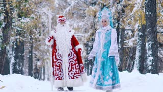 Man and woman dressed in New Year costume having fun in winter forest