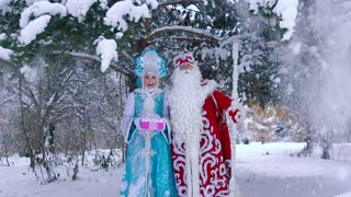 Man and woman dressed in New Year costumes standing under snowy tree