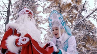 Man and woman in New Year costumes on Christmas Eve are happy to see the gifts