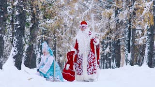 Man in costume of Father Frost and woman in costume of Snowflake having fun in forest
