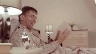Man in spectacles is sitting in bed with a book and laughing his pleasure