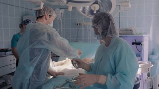 Medical assistant filling water syringes for surgeons to use them during the operation