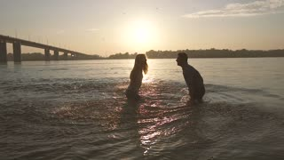 Playful couple spraying with water in the river