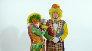 Portrait of a couple of circus clowns having fun together against white background
