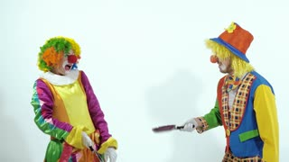 Portrait of a couple of comic circus clowns pretending kung fu fighters with frying pans