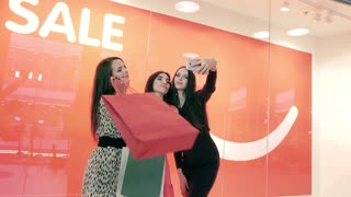 Portrait of attractive women taking photos after successful shopping