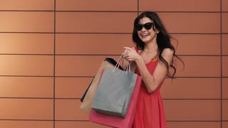 Portrait of beautiful young brunette girl holding shopping bags