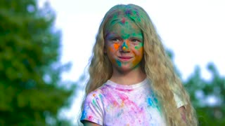 Portrait of cute blonde little girl after a holy powder battle