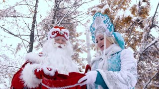 Portrait of Ded Moroz Father Frost and Snegurochka Snow Maiden picking up the bag to look into it