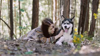 Portrait of eye-catching girl lying in the forest with her dog