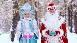 Portrait of Father Frost and smiling Snow Maiden showing gifts to the camera