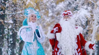 Portrait of Father Frost and Snow Maiden walking in the forest and enjoying the landscape
