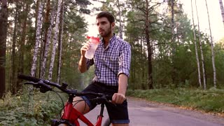 Portrait of handsome man sitting on bike and drinking water