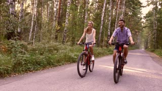 Portrait of happy couple having fun on bicycle ride in the summer park