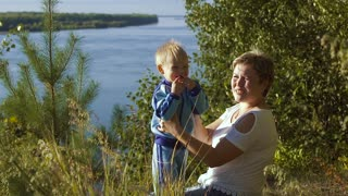 Portrait of happy mother and her little son sitting against river background on a sunny summer day
