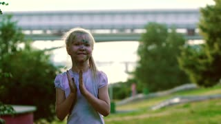 Portrait of little blond girl in city park clapping her hands, jumping and turning around