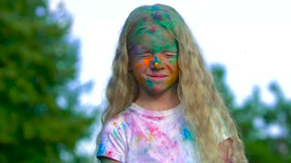 Portrait of little blonde girl being attacked with holy powder