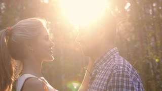 Portrait of loving couple standing in sunbeams looking into each other is eyes