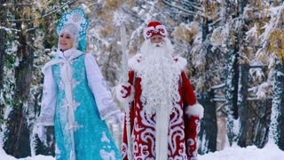 Portrait of man and woman in New Year costumes walking in forest and enjoying landscape