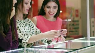 Portrait of pretty women in jewelry store buying bracelet