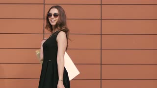 Portrait of shopping woman turning around with shopping bags. Slow motion