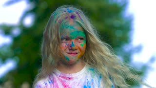 Portrait of smiling blond little girl with dye on her face looking at the camera and throwing the holy powder