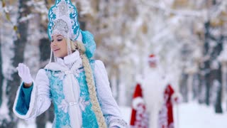 Portrait of smiling Snow Maiden and Father Frost in the background enjoying the walk in the forest
