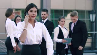Portrait of stylish young business woman talking on the phone and her smart-looking coworkers standing and talking to each other
