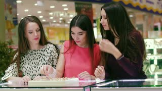 Portrait of three female friends looking and trying on rings in shopping mall