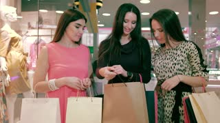 Portrait of three smiling young women in shop center talking about clothes