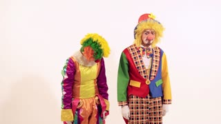 Portrait of two circus clowns kicking friendly and teasing each other