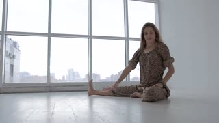 Portrait of woman practicing yoga alone in studio against windows background