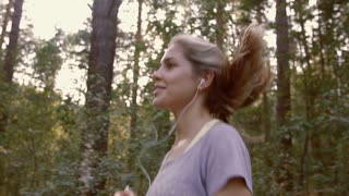 Portrait of young cheerful woman jogging along the forest path