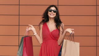 Portrait of young smiling woman showing her shopping bags
