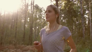 Portrait of young woman jogging in the forest