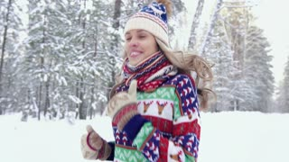 Pretty blond woman running in the forest on a winter day