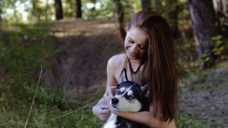 Pretty fair-skinned young woman sitting on knees and hugging dog is happy pan