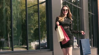 Pretty shopping woman dances holding shopping bags on the street. Slow motion