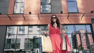 Pretty young girl in red dress holding her shopping bags