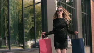Pretty young woman in black dress jumps in excitement with shopping bags