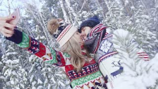 Romantic couple in snowy forest kissing and taking selfie