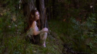 Romantic young woman sitting in the wood alone and touches her legs and palms as she is a bit cold.