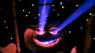 Shining in the lights pumpkin is comes nearer surrounded with smoke