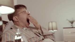 Sleepy young man yawning in bed, putting spectacles away and going to sleep