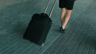 Slender woman legs in black high heels shoes walking with travel luggage