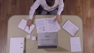 Smart-looking businessman sitting at his table finishes his work