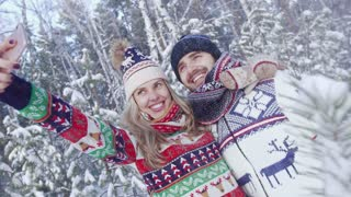 Smiling blond woman and handsome young man taking photo of themselves in snowy forest